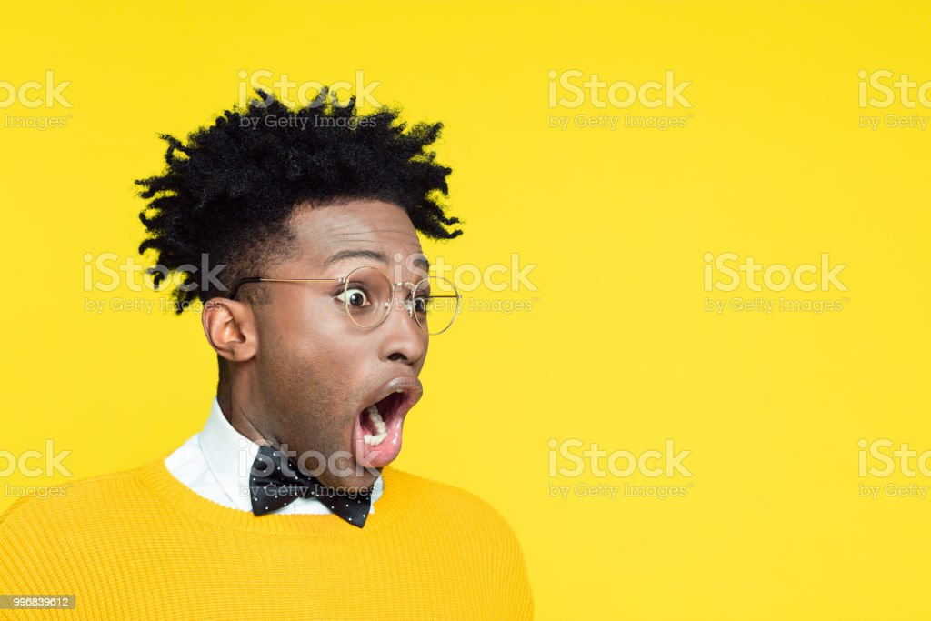 Portrait of surprised geeky young man looking away stock photo