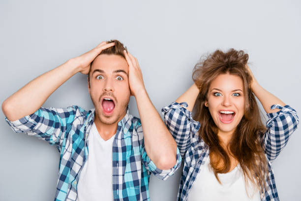 portrait of surprised man and woman screaming and touching hair - sorpresa foto e immagini stock