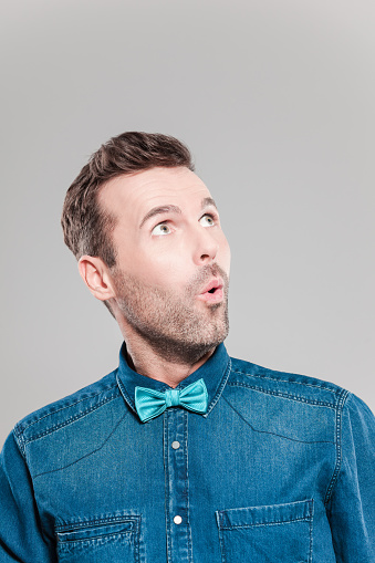Portrait Of Surprised Man Wearing Jeans Shirt And Bow Tie Stock Photo - Download Image Now