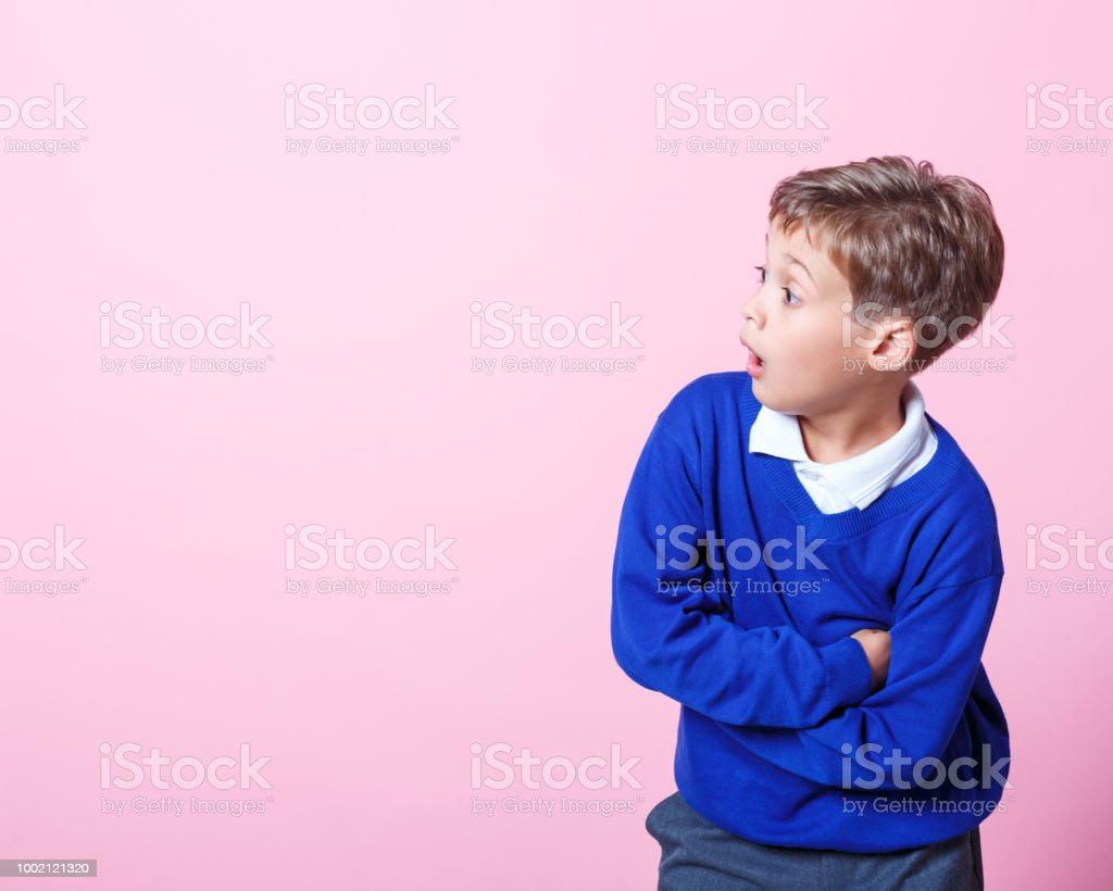 Portrait of surprised schoolboy looking away with mouth open Shocked schoolboy wearing school uniforms looking away with mouth open. Studio shot, pink background. 8-9 Years Stock Photo