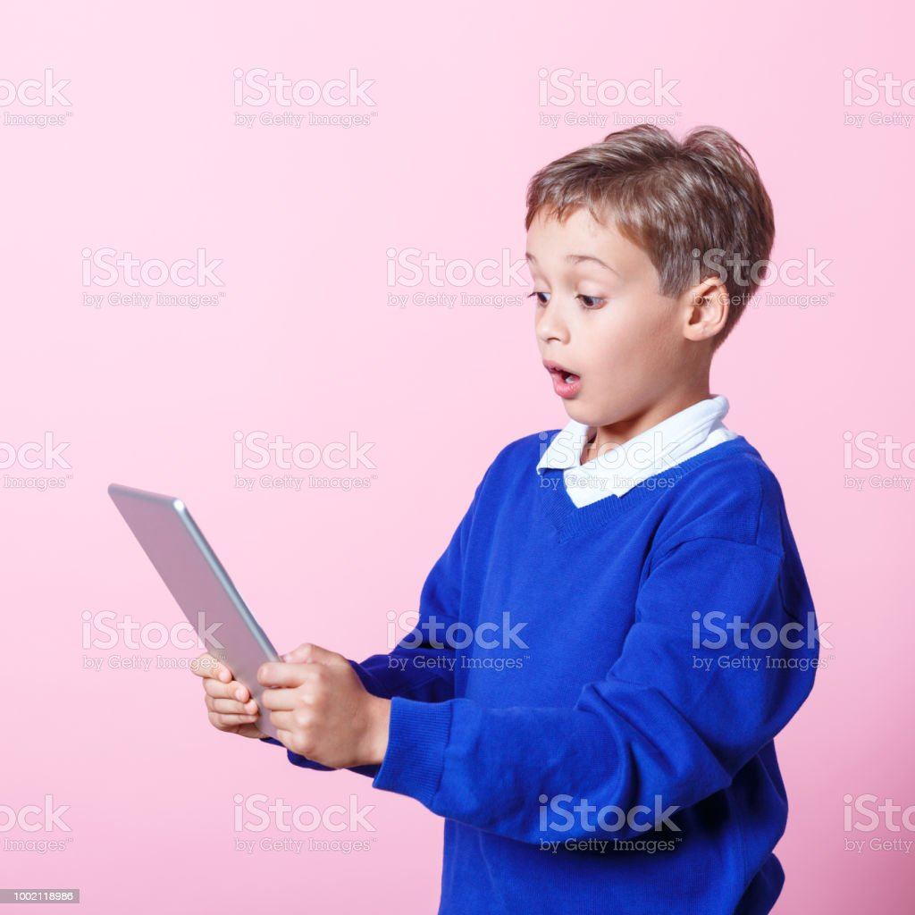 Portrait of surprised schoolboy using a digital tablet Surprised schoolboy wearing school uniforms using a digital tablet. Studio shot, pink background. 8-9 Years Stock Photo
