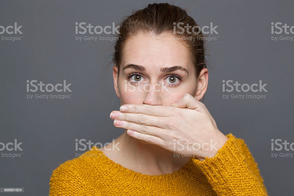 portrait of surprised young woman covering her mouth for silence stock photo