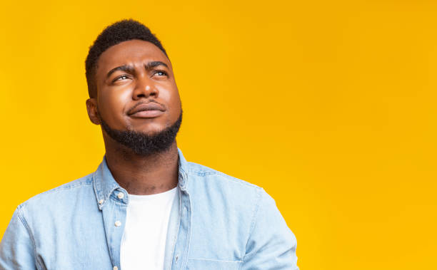 Portrait of suspicious black guy looking upwards at copy space Portrait of suspicious black guy looking upwards at copy space on yellow background. smirking stock pictures, royalty-free photos & images