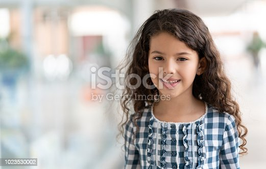 istock Portrait of sweet 8 year old little girl looking at camera smiling 1023530002