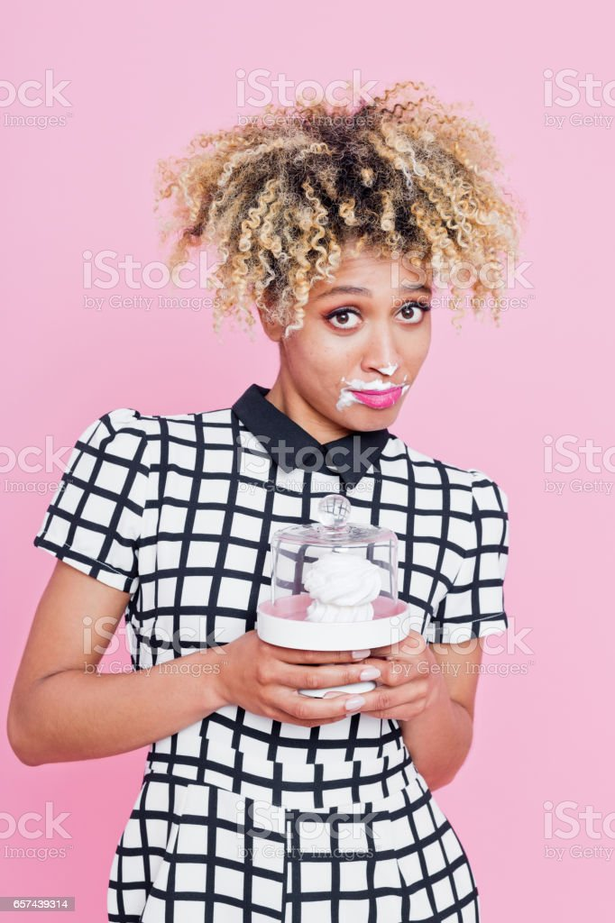 Portrait of sweet afro american young woman eating meringue Studio portrait of cute afro american young woman eating meringue, looking at camera. Pink background. 20-24 Years Stock Photo