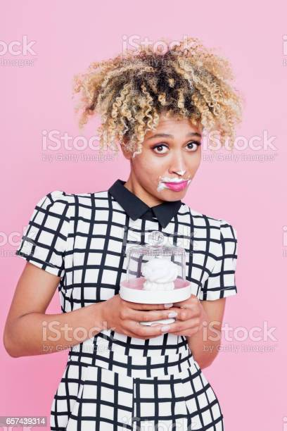 Portrait Of Sweet Afro American Young Woman Eating Meringue Stock Photo - Download Image Now