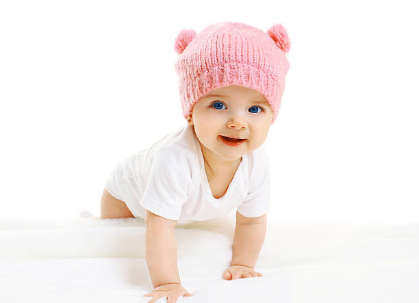 Portrait of sweet baby crawls in the pink knitted hat stock photo