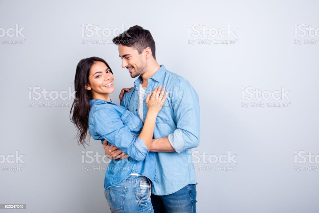 Portrait of sweet hispanic cute lovers, bearded man hugging woman and looking at her, pretty woman looking at camera over grey background stock photo