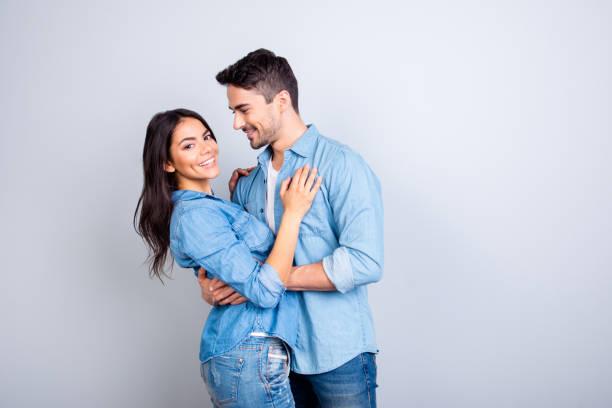 甘いヒスパニック系のかわいい恋人の肖像画ひげを生やした男性女性を抱き締めると、彼女を見てきれいな灰色の背景の上のカメラを探している女性 - ボーイフレンド ストックフォトと画像