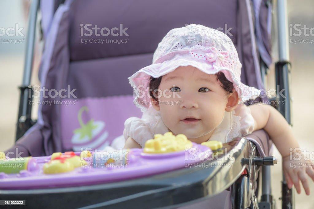 Portrait of sweet little asian baby girl sitting in stroller. stock photo