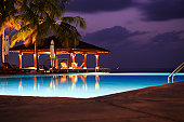 A beautiful portrait of a swimming  pool at a holiday destination at night.