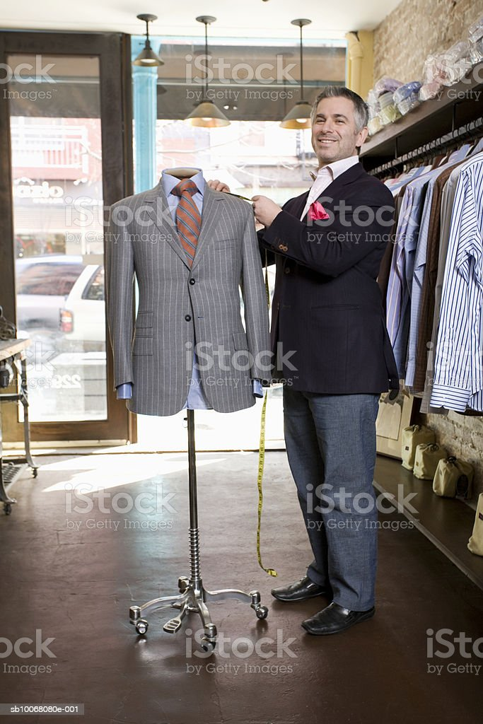 Portrait of tailor by dressmaker's model in store royalty-free stock photo