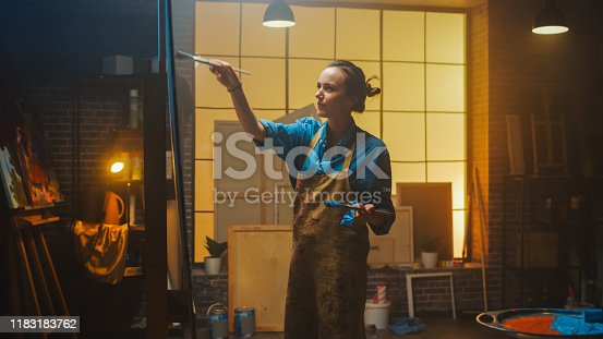 910798810 istock photo Portrait of Talented Female Artist Working on a Modern Abstract Oil Painting, Gesturing with Broad Strokes Using Paint Brush. Dark Creative Studio Large Picture Stands on Easel Illuminated. Low Angle 1183183762