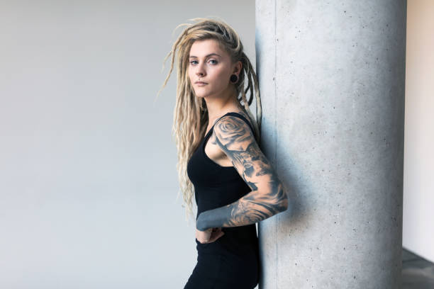 Portrait of tattooed and pierced young women with blond dreadlocks stock photo