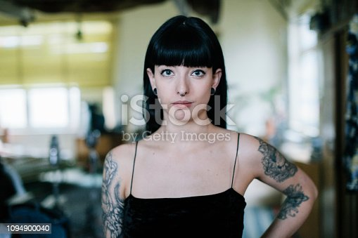 Portrait of tattooed woman standing in her apartment.