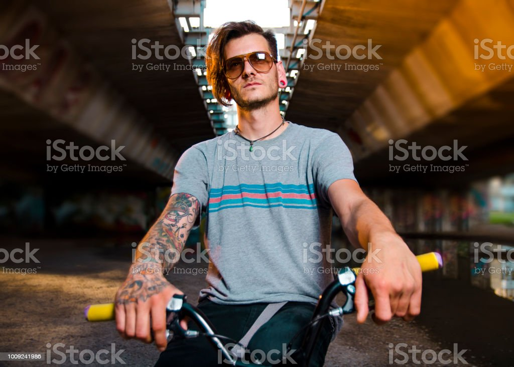 Portrait of tattooed young adult man on BMX bike stock photo