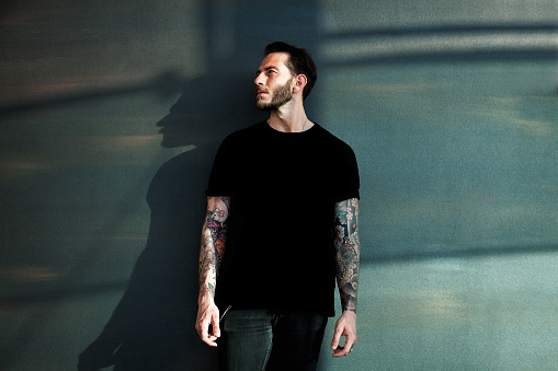 Portrait of tattooed young man with black t-shirt
