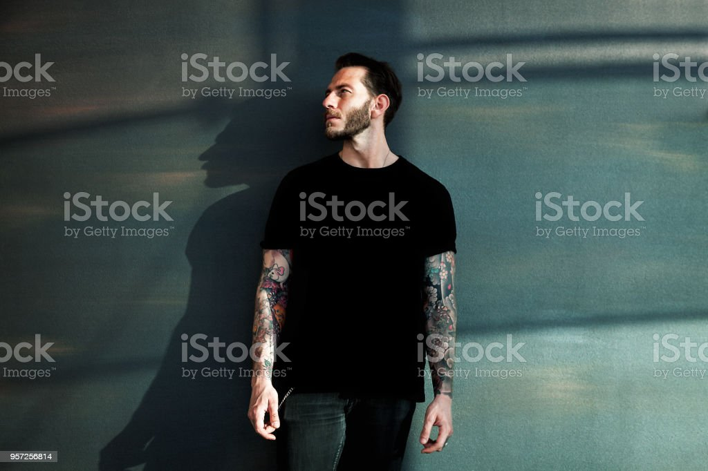 Portrait of tattooed young man with black t-shirt stock photo