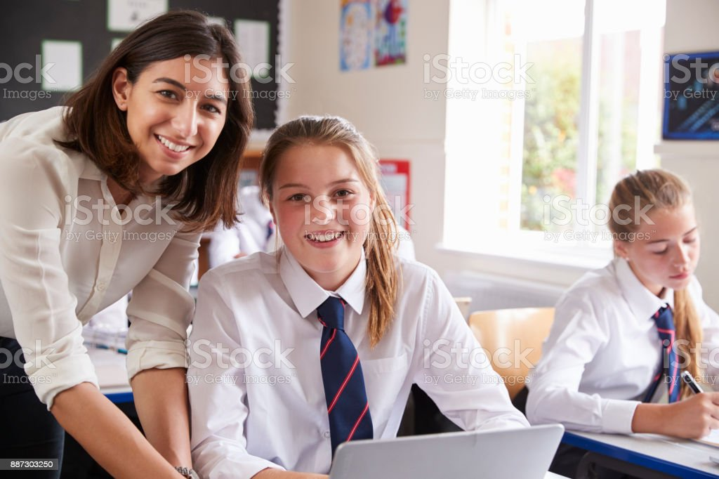 Portrait Of Teacher Helping Pupil Using Computer In Classroom stock photo