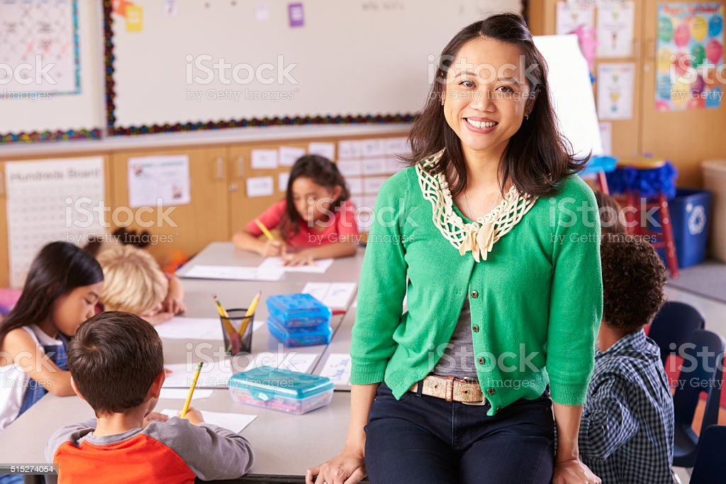 Portrait of teacher in classroom with elementary school kids stock photo
