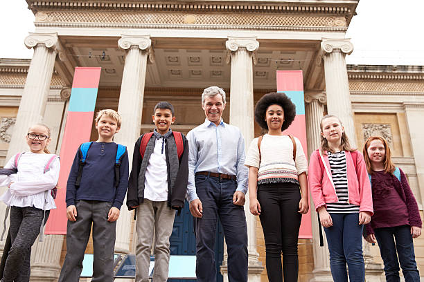 Portrait Of Teacher With Class Standing Outside Museum Portrait Of Teacher With Class Standing Outside Museum field trip stock pictures, royalty-free photos & images