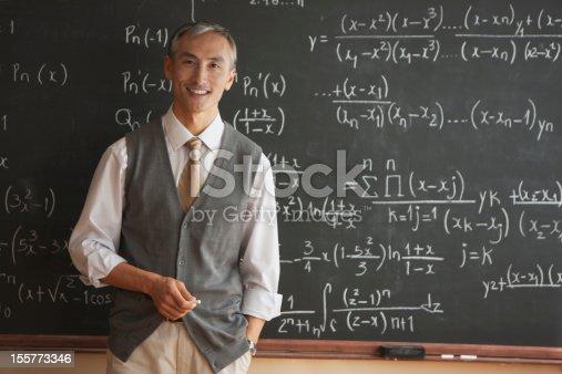 istock Portrait of teacher with in front of blackboard 155773346