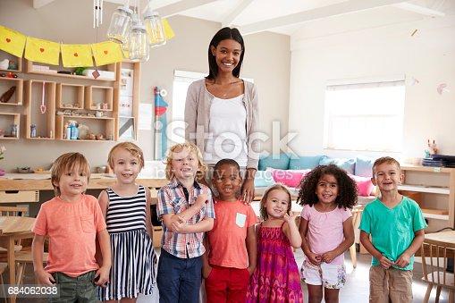 684059604 istock photo Portrait Of Teacher With Pupils In Montessori School Classroom 684062038