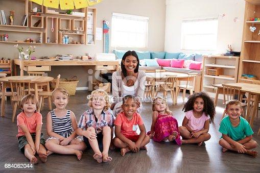 684059604 istock photo Portrait Of Teacher With Pupils In Montessori School Classroom 684062044