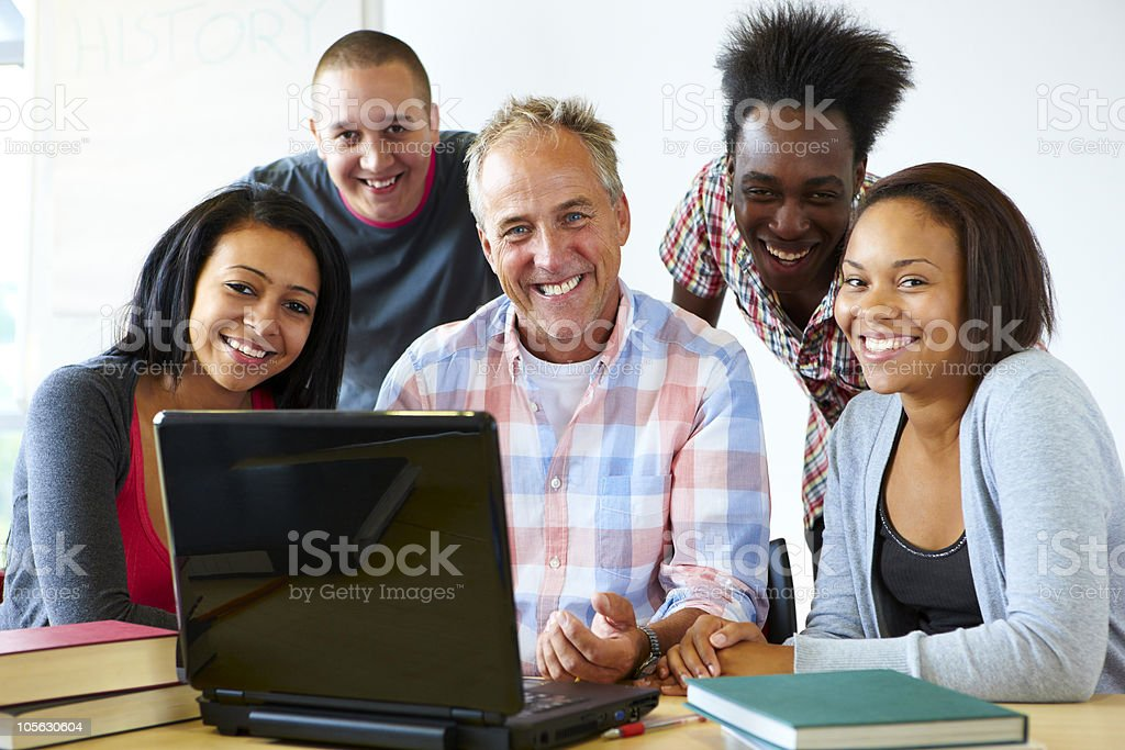 portrait of teacher with students looking at laptop royalty-free stock photo