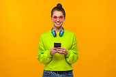 istock Portrait of teen girl wearing neon green sweatshirt, pink glasses and headphones on neck, standing with phone in hand, isolated on yellow background 1256944035