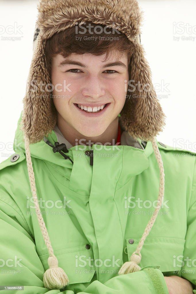 Portrait Of Teenage Boy In Snow Wearing Fur Hat stock photo
