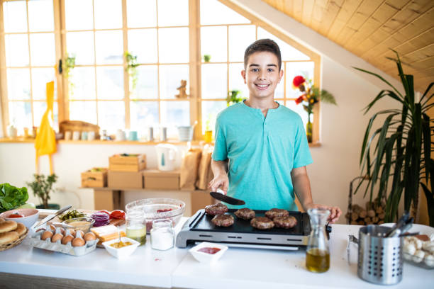 Portrait of Teenage boy while  grilling burgers in the kitchen stock photo