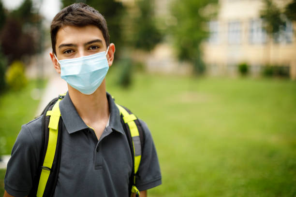 Portrait of teenage boy with face protective mask in front of the school stock photo