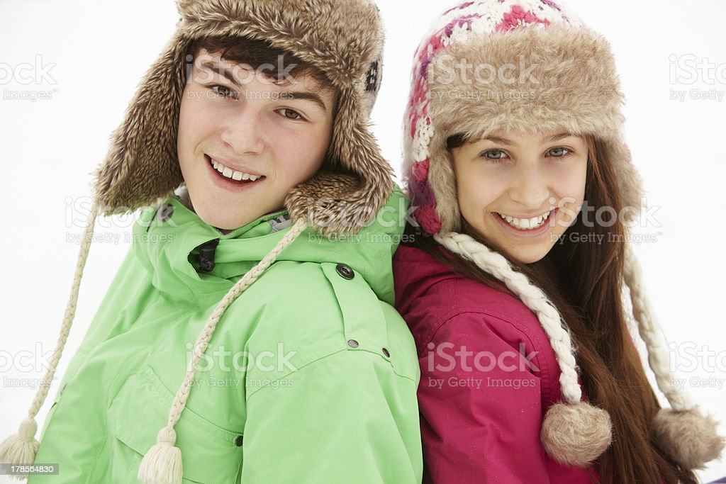 Portrait Of Teenage Couple In Snow Wearing Fur Hats stock photo