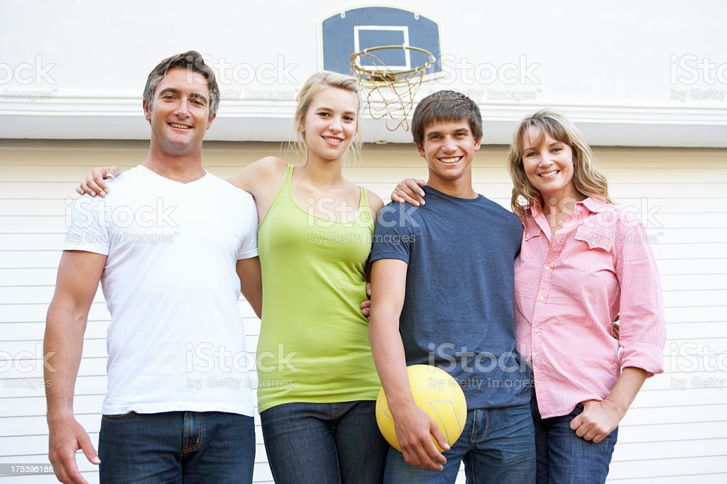 Portrait Of Teenage Family Playing Basketball Outside Garage royalty-free stock photo
