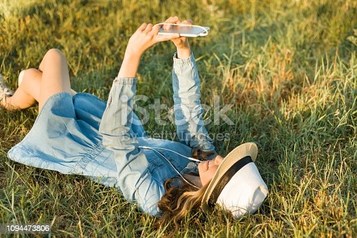 Portrait of teenage girl 14 years old lying on the grass. Girl in dress hat, in her headphones holds a smartphone, listens to music makes a selfi photo. View from above.