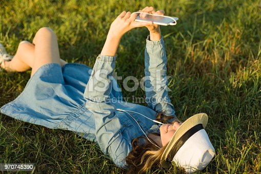 Portrait of teenage girl 14 years old lying on the grass. Girl in dress hat, in her headphones holds a smartphone, listens to music makes a selfi photo. View from above