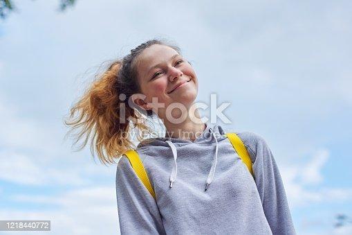 Portrait of teenage girl 15 years old, smiling pretty girl in gray sweatshirt, background sky