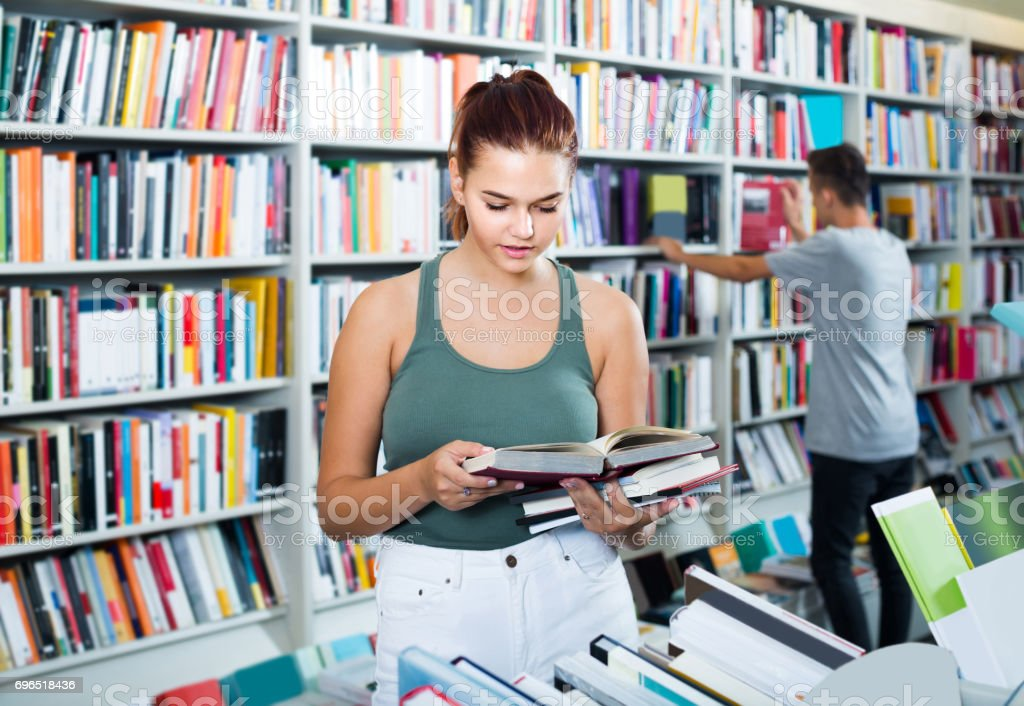 portrait of  teenage girl customer looking at open book standing among bookshelves stock photo
