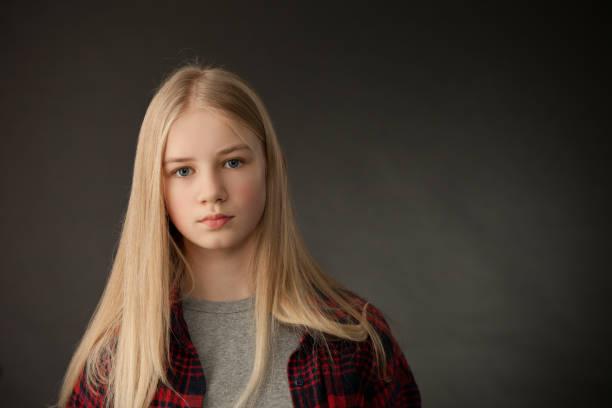 Portrait of teenage girl in studio on black background stock photo