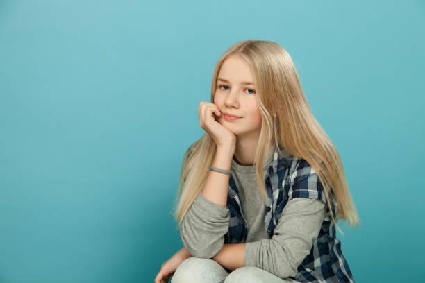 Portrait of teenage girl in studio on blue background stock photo