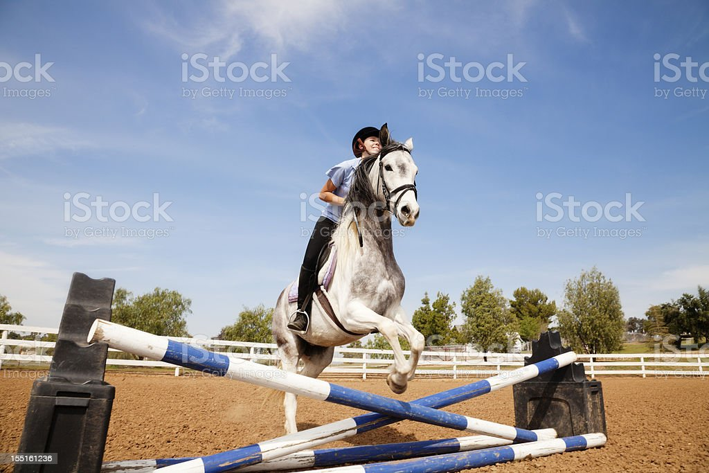 Portrait of teenage girl jumping on a horse stock photo
