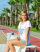 Blonde, young girl near bicycle path with tall palms. Sunny summer days
