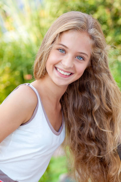 Portrait of teenage girl with gorgeous blond hair posing outdoors stock photo