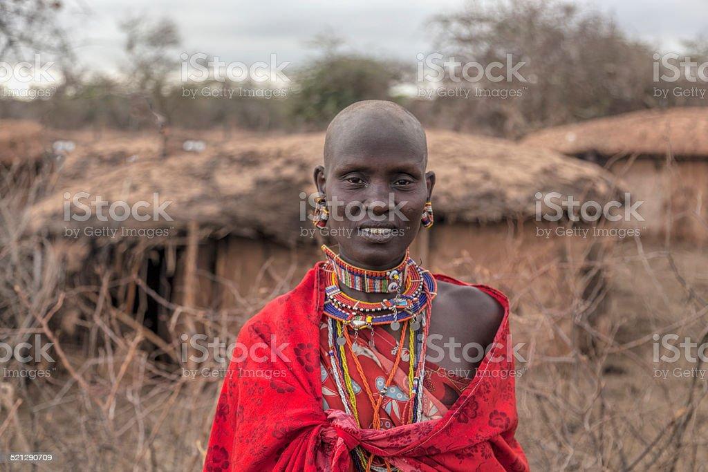 Portrait of teenage Maasai girl in traditional dress outside hut. stock photo
