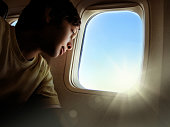 Portrait of teenager boy looking through airplane window and beam of light coming from window