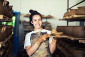 Teenager girl working in family factory for pottery, she holding clay vessels, workshop