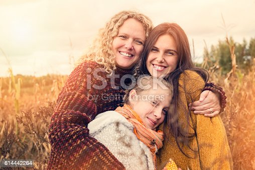 istock Portrait of teenagers with mother in autumn sunset outdoors. 614442264