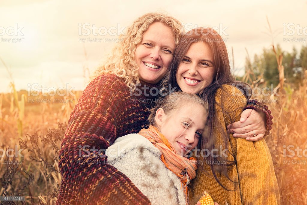 Portrait of teenagers with mother in autumn sunset outdoors. stock photo