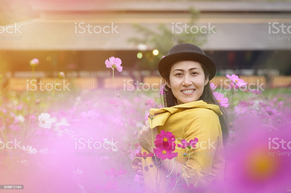Portrait of thai women at the beautiful cosmos flowers field. stock photo